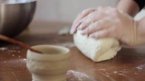 Mãos da mulher que amassam a massa na tabela cozinhando o alimento em uma cozinha video estoque