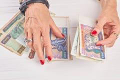 Mãos da mulher que contam o dinheiro do kyat Foto de Stock
