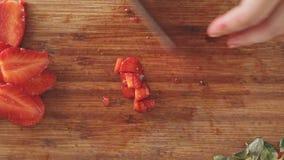 Mãos da mulher que cortam morangos na placa de corte de madeira vídeos de arquivo