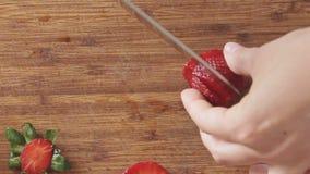 Mãos da mulher que cortam morangos na placa de corte de madeira filme