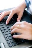 Mãos da mulher que datilografam no portátil Fotografia de Stock