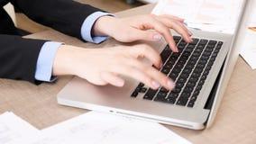 Mãos da mulher que datilografam no teclado do portátil video estoque