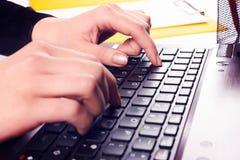 Mãos da mulher que datilografam no teclado do portátil Imagens de Stock