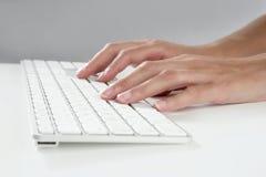 Mãos da mulher que datilografam o teclado Imagens de Stock