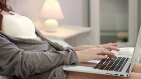Mãos da mulher que datilografam o teclado do portátil na cama Mãos fêmeas que datilografam o teclado filme