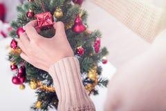 Mãos da mulher que decoram a árvore de Natal Foto de Stock Royalty Free