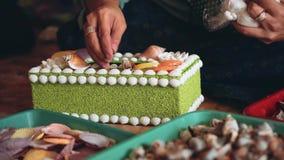 Mãos da mulher que decoram o caixão com conchas do mar filme