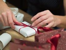 Mãos da mulher que envolvem presentes do Natal Imagem de Stock Royalty Free