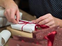 Mãos da mulher que envolvem presentes do Natal Fotografia de Stock