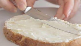 Mãos da mulher que espalham o queijo creme no pão filme