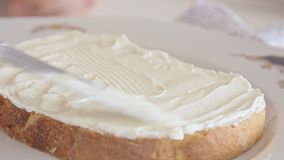 Mãos da mulher que espalham o queijo na fatia do pão vídeos de arquivo