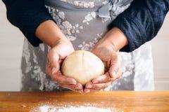 Mãos da mulher que fazem o pão fotografia de stock