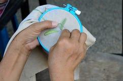 Mãos da mulher que fazem o ponto de cruz Fotografia de Stock
