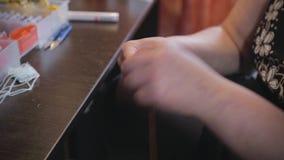 Mãos da mulher que fazem o ponto de cruz do bordado filme