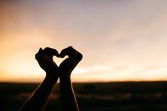 Mãos da mulher que fazem um coração Fotos de Stock