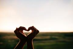 Mãos da mulher que fazem um coração Imagens de Stock Royalty Free