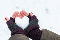 Mãos da mulher que guardam a bola de neve dada forma coração imagens de stock