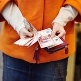 Mãos da mulher que guardam a bolsa com rublos de russo Fotografia de Stock