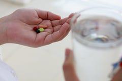 Mãos da mulher que guardam comprimidos e vidro de água Foto de Stock Royalty Free