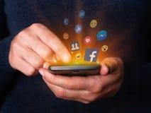 Mãos da mulher que guardam e que usam da verificação móvel do telefone celular do smartphone a rede social app dos meios de Faceb fotografia de stock royalty free