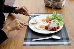 Mãos da mulher que guardam a faca e a forquilha durante comer o café da manhã fotografia de stock royalty free