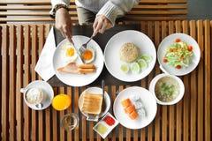 Mãos da mulher que guardam a faca e a forquilha durante comer o café da manhã fotos de stock royalty free