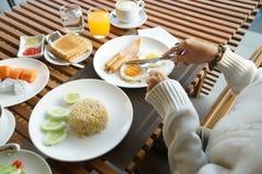 Mãos da mulher que guardam a faca e a forquilha durante comer o café da manhã fotografia de stock