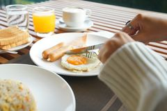 Mãos da mulher que guardam a faca e a forquilha durante comer o café da manhã imagens de stock