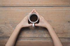 Mãos da mulher que guardam o copo de café Imagem de Stock