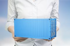 Mãos da mulher que guardam o recipiente de carga 3d azul Foto de Stock Royalty Free