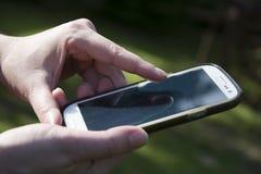Mãos da mulher que guardam o smartphone foto de stock royalty free