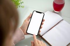 Mãos da mulher que guardam o telefone do toque com a tela isolada acima da tabela no escritório fotografia de stock royalty free