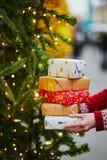 Mãos da mulher que guardam a pilha de presentes de Natal fotografia de stock