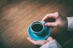 Mãos da mulher que guardam pouca xícara de café azul Fotografia de Stock
