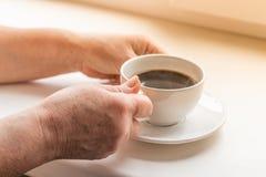 Mãos da mulher que guardam um café quente fotografia de stock