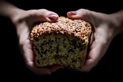 Mãos da mulher que guardam um naco de pão imagens de stock