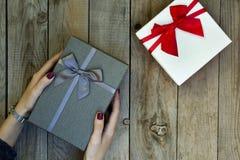 Mãos da mulher que guardam uma caixa de presente na tabela de madeira imagem de stock royalty free