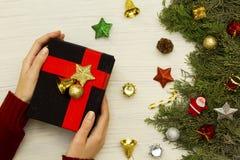Mãos da mulher que guardam uma caixa de presente preta do Natal no fundo branco imagem de stock