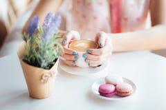 Mãos da mulher que guardam a xícara de café Macarons na tabela e na alfazema imagens de stock royalty free