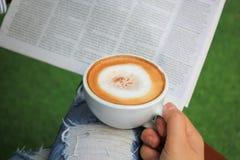 Mãos da mulher que guardam xícaras de café quentes com espuma e jornal do leite na manhã no fundo verde fotos de stock