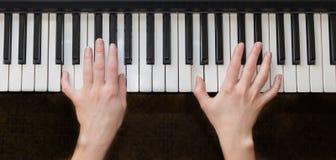 Mãos da mulher que jogam a música do piano Fotografia de Stock