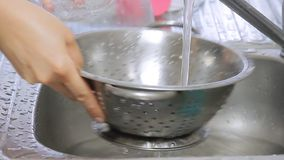 Mãos da mulher que lavam mirtilos sob o córrego da água vídeos de arquivo