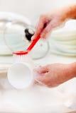 Mãos da mulher que lavam pratos fotografia de stock royalty free