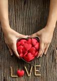 Mãos da mulher que mantêm o coração vermelho dado forma Foto de Stock