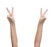 Mãos da mulher que mostram o v-sinal Foto de Stock