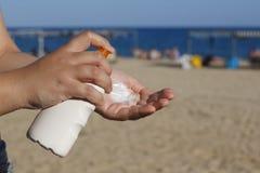 Mãos da mulher que põem a proteção solar na praia fotografia de stock