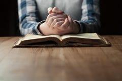 Mãos da mulher que rezam com uma Bíblia Imagens de Stock Royalty Free