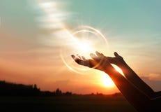 Mãos da mulher que rezam no fundo do por do sol foto de stock royalty free