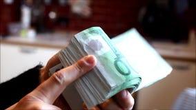 Mãos da mulher que seguram um punhado de contas de cem-Euro vídeos de arquivo