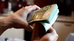 Mãos da mulher que seguram um punhado de contas de cem-Euro filme